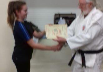 Cara receives her 8th KYU certificate from Sensei Reg