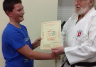 Kieran receives his 8th KYU certificate from Sensei Reg