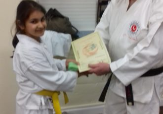 Amrita receives her 6th KYU certificate from Sensei Reg