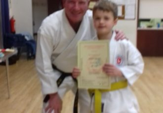 Henry receives his 6th KYU certificate from Sensei Mick
