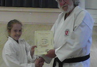 Orla receives a special recognition award from Sensei Reg for achieving the first ever triple grade